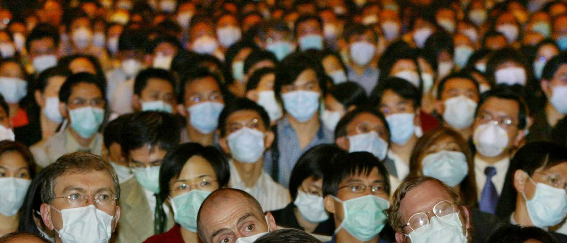 Doctors and health care workers wearing face masks attend a symposium on Severe Acute Respiratory Syndrome (SARS) in Hong Kong 25/04/2003.