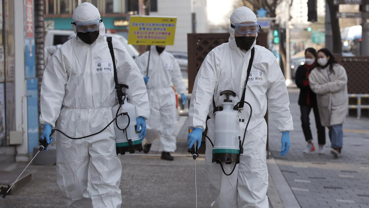 South Korean soldiers wearing protective gear spray disinfectant as a precaution against the new coronavirus on a street in Seoul, South Korea. Picture: AP