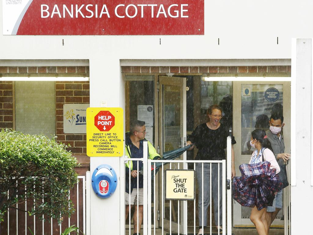Parents wearing masks arrive to pick their children up from Banksia Cottage Childcare within the Macquarie University Campus. Picture: John Appleyard