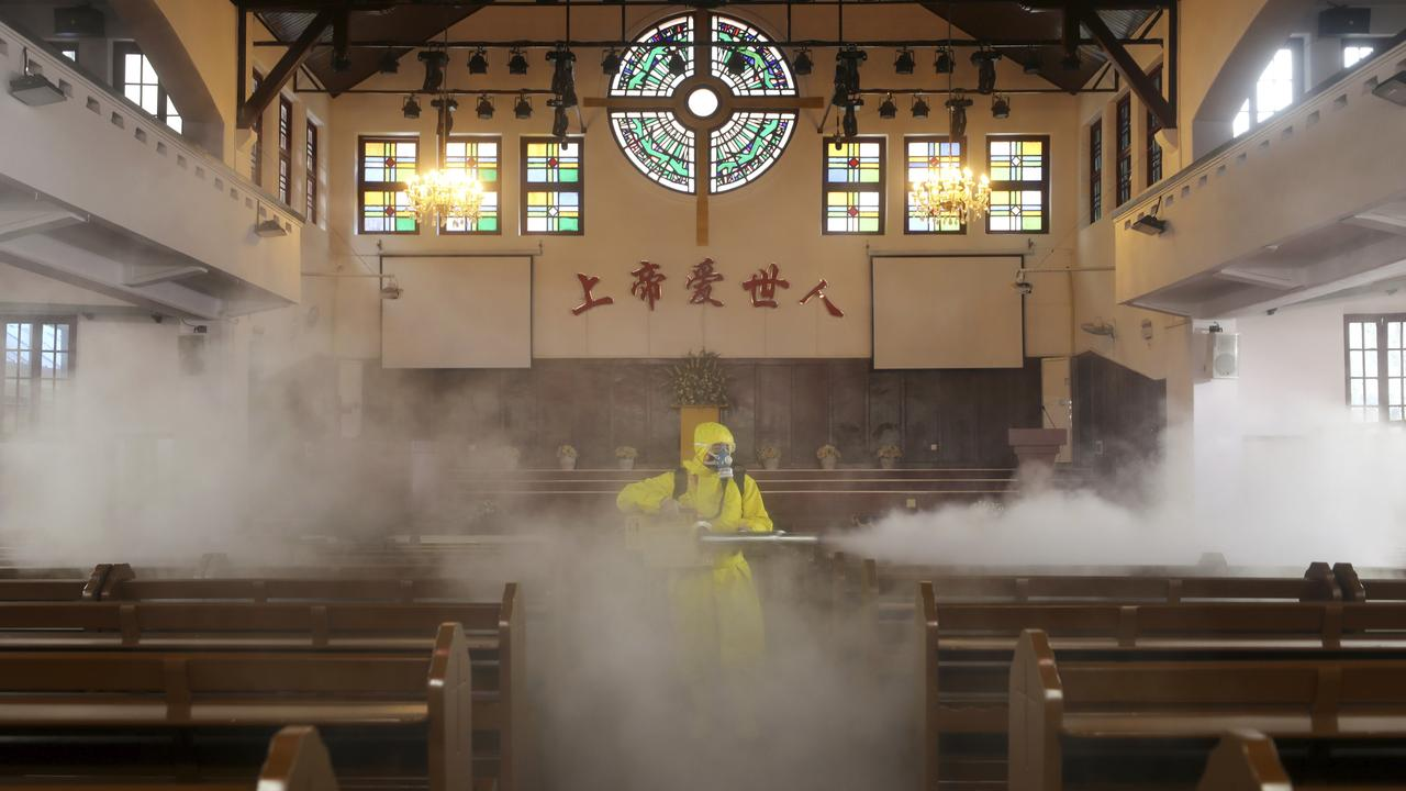 A volunteer sprays disinfectant inside a Christian church in Wuhan in central China's Hubei Province, Friday, March 6, 2020.