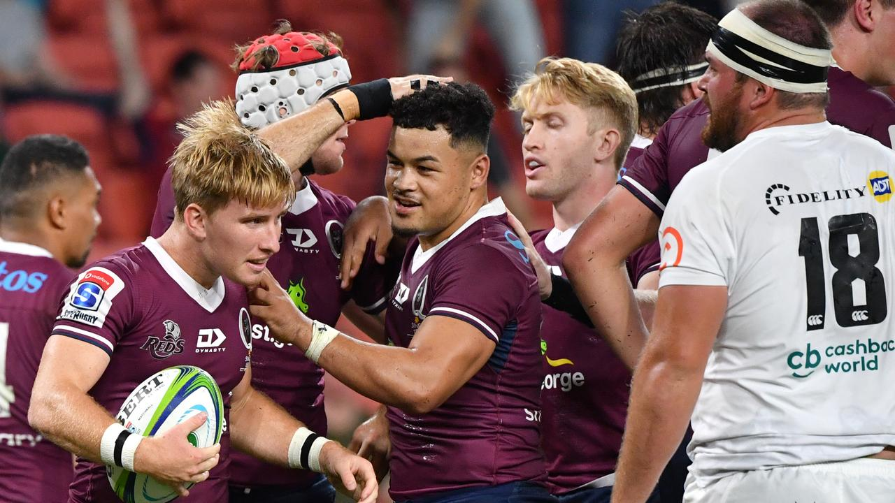 Tate McDermott (second from left) celebrates scoring a try with teammates against the Sharks last month.