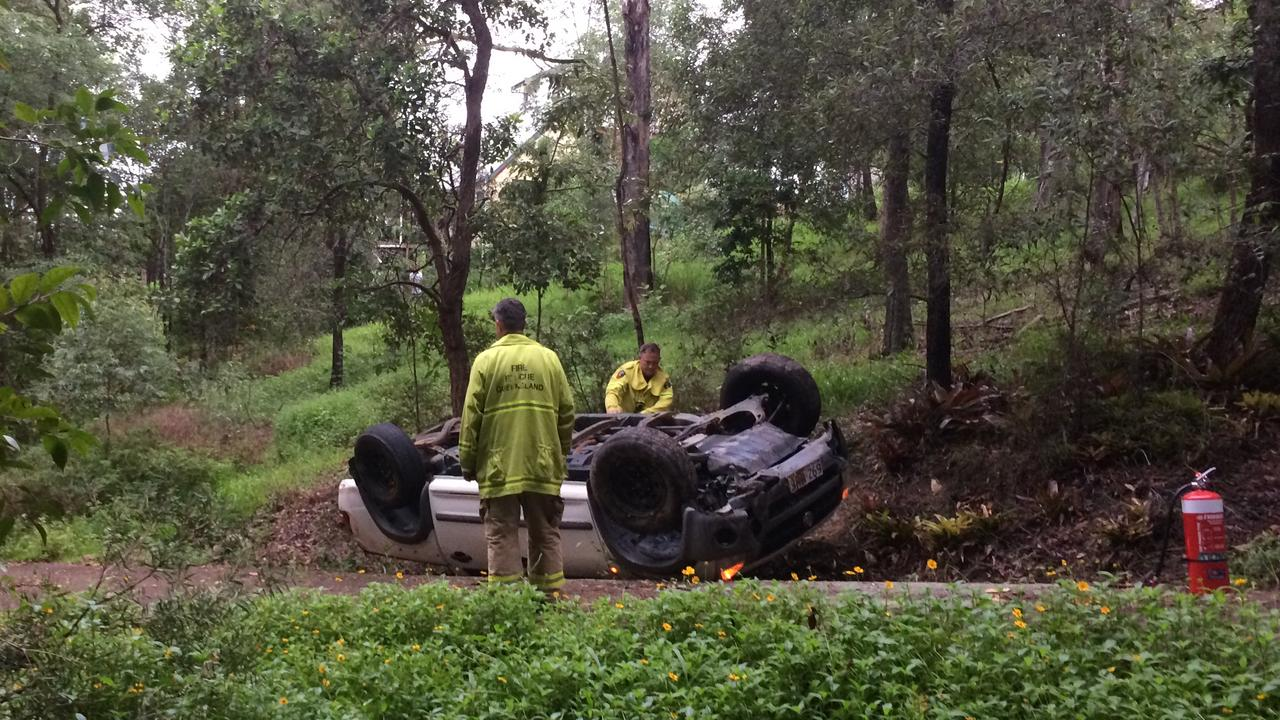 Firefighters prepare a ute to be recovered after it rolled in a driveway on Cogill Rd at Buderim.