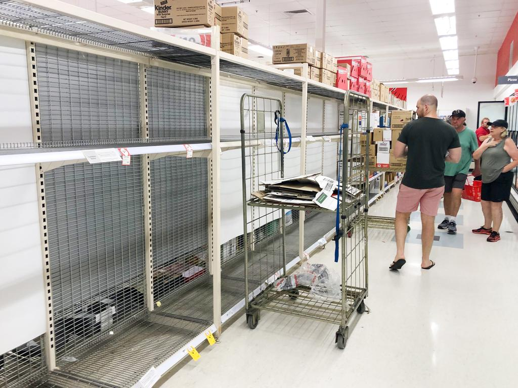 Customers ponder their choices as toilet paper is completely sold out at Coles Mooloolaba due to coronavirus fears.