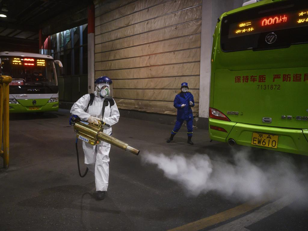 A Chinese Blue Sky Rescue volunteer fumigates and disinfects an area of a local bus station in Beijing, China. Picture: Kevin Frayer/Getty