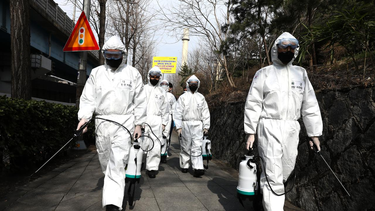 SEOUL, SOUTH KOREA – MARCH 09: South Korean soldiers, wearing protective gear, spray antiseptic solution to guard against the coronavirus (COVID-19) along a street in Gangnam district on March 09, 2020 in Seoul, South Korea. The South Korean government has raised the coronavirus alert to the