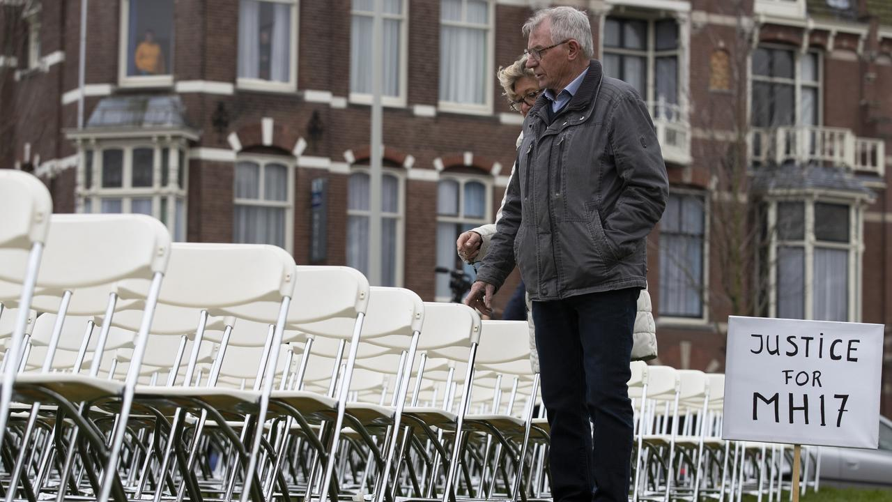 Relatives walk along 298 empty chairs, each chair for one of the 298 victims of the downed Malaysia Air flight MH17, are placed in a park opposite the Russian embassy in The Hague, Netherlands. Picture: AP/Peter Dejong