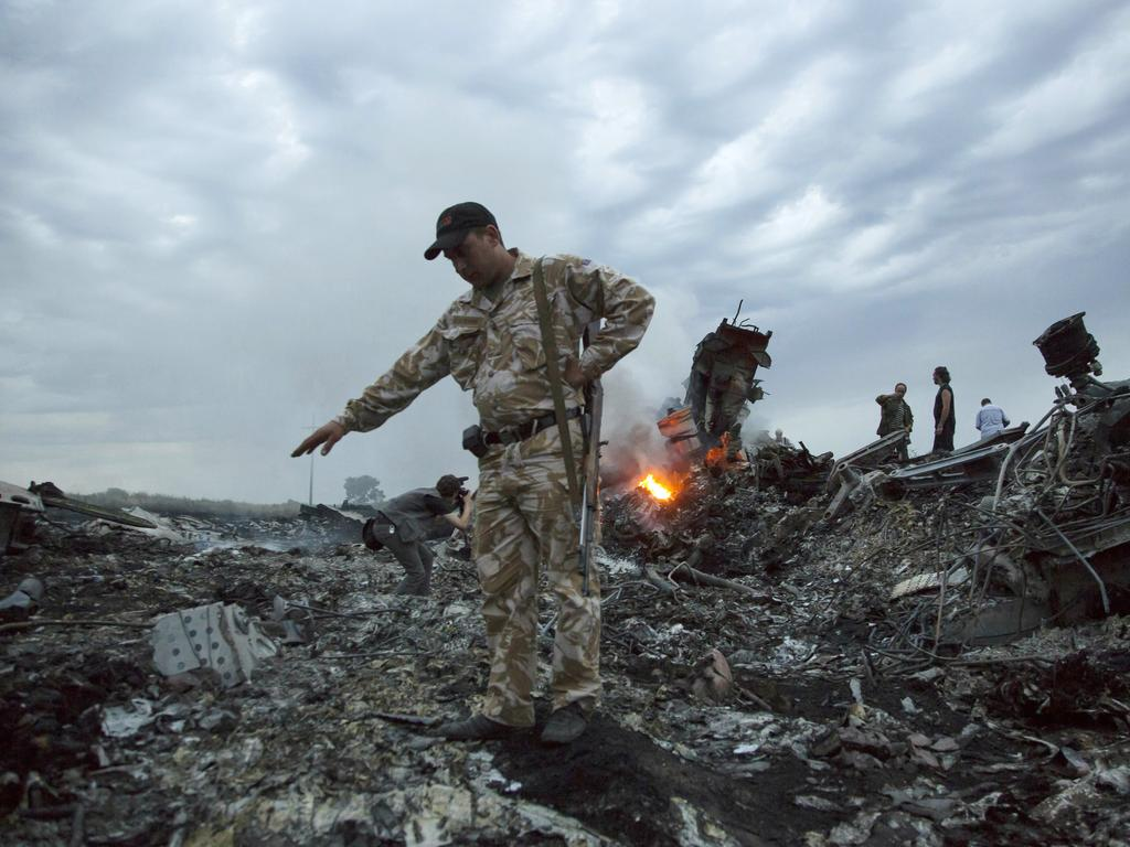People walk among the debris at the crash site of MH17 passenger plane near the village of Grabovo, Ukraine, that killed 298 people killed. Picture: AP