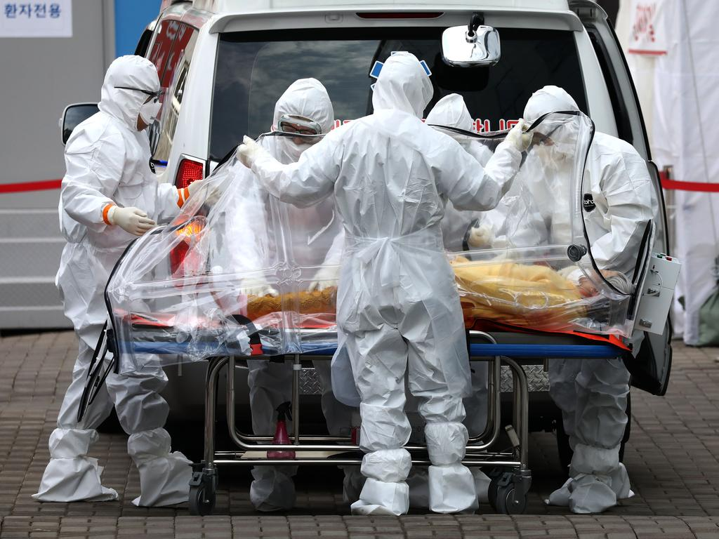 Medical staff move a patient infected with the coronavirus from an ambulance to a hospital in Seoul, South Korea. Picture: Getty Images