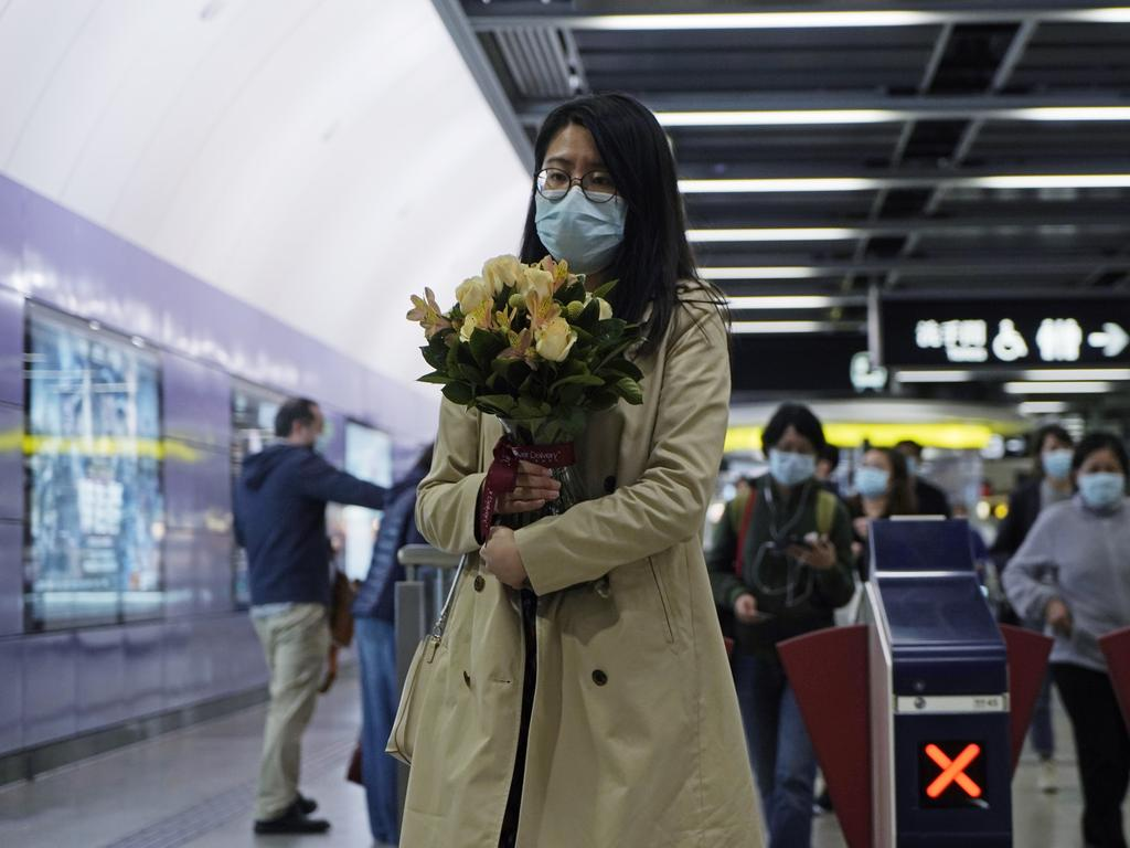 A woman wearing a mask holds a bunch of flower as a precaution against coronavirus, at a subway station in Hong Kong. Picture: AP