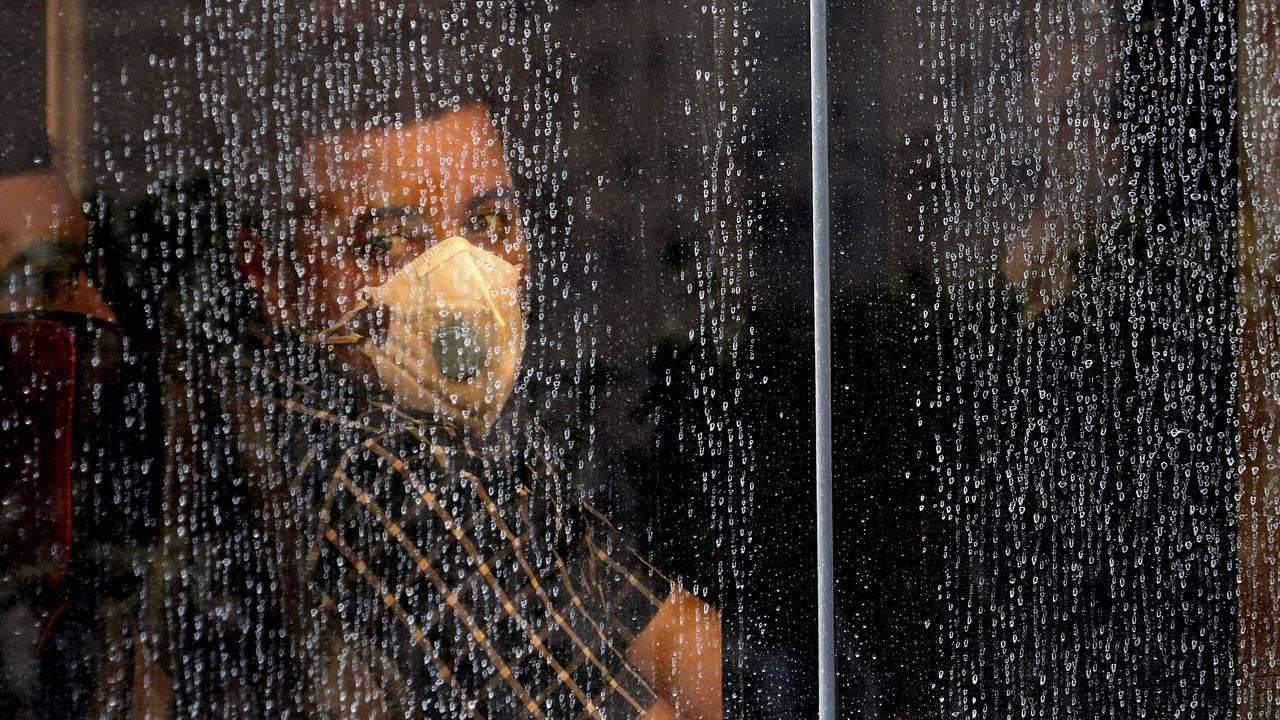A commuter looks through a water-stained window wearing a mask and gloves to help guard against the Coronavirus, on a public bus. (AP Photo/Ebrahim Noroozi)