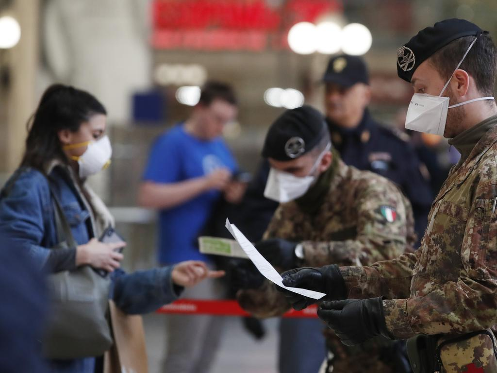 Police officers and military personnel in Milan have been grilling people on how essential their travel is. Picture: Antonio Calanni/AP