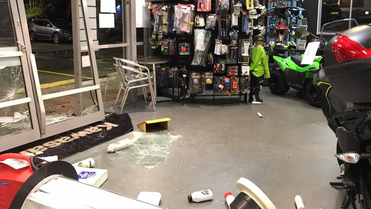 The damage left behind at Mackay Kawasaki after thieves used a stolen red LandCruiser to ram and raid the store and steal a motorbike.