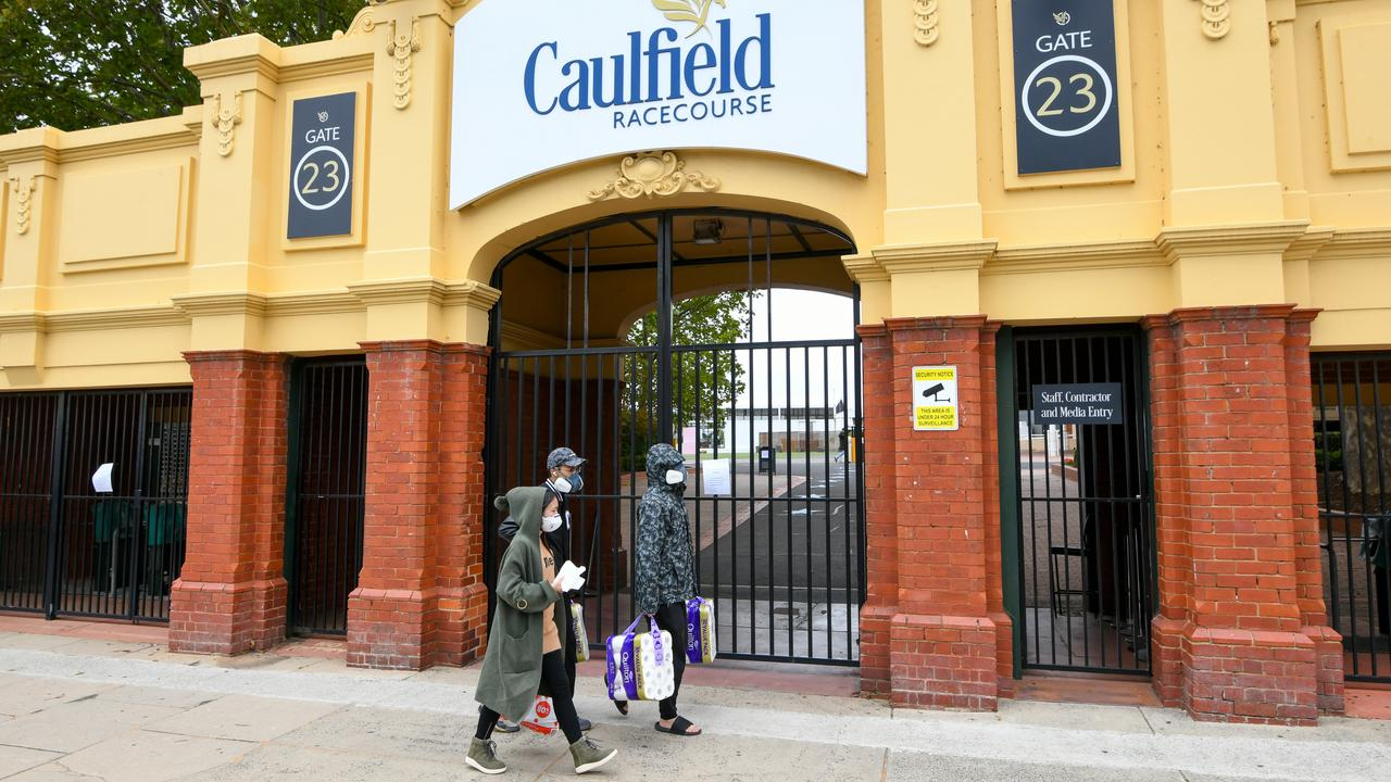 People wearing masks and carrying toilet paper walk past Caulfield Racecourse in Melbourne on Saturday. Picture: Vince Caligiuri/AAP
