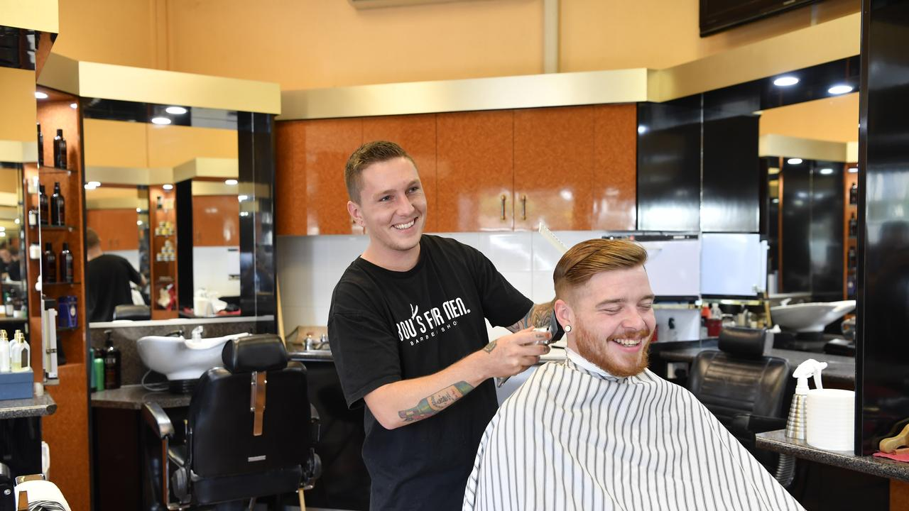 It is work as usual for barber Addison Manning and customer Sean McMeekin.
