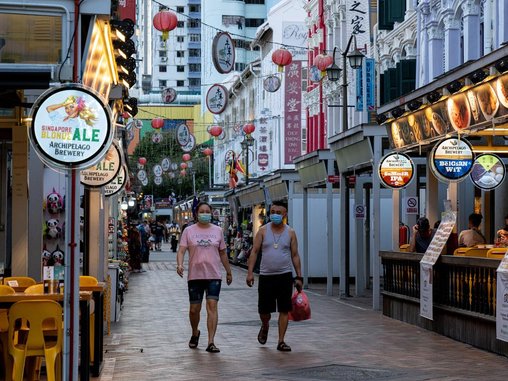 People wearing masks walk on the street in Chinatown in Singapore. Picture: Getty