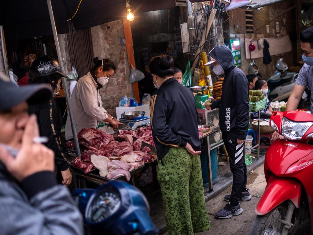 People wear face masks amid concerns of the spread of the COVID-19 coronavirus while shopping at a local market on in Hanoi, Vietnam.