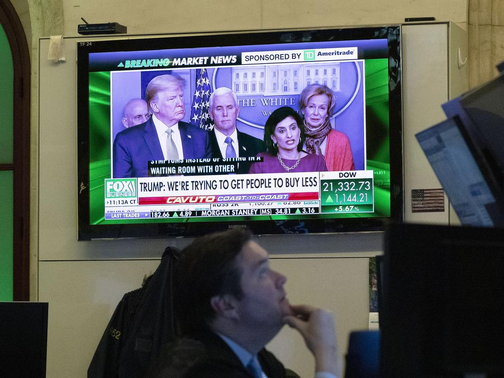 A trader at the New York Stock Exchange listen to President Donald Trump's televised White House news conference. Picture: AP