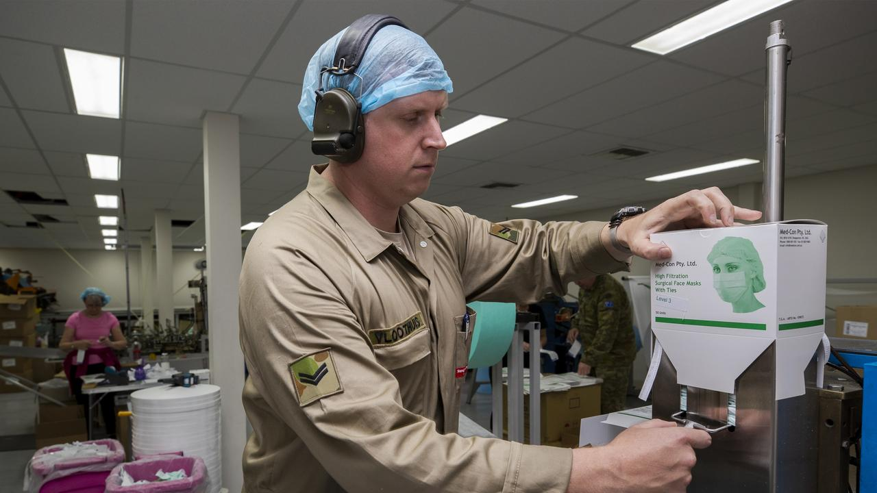 Australian Army soldier Corporal Sander Vloothuis operates the surgical face mask machine at Med-Con Pty Ltd. Picture: Defence