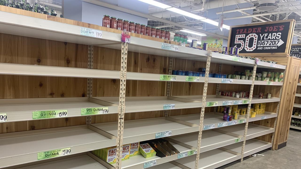 Near-empty shelves in a Trader Joe's supermarket.