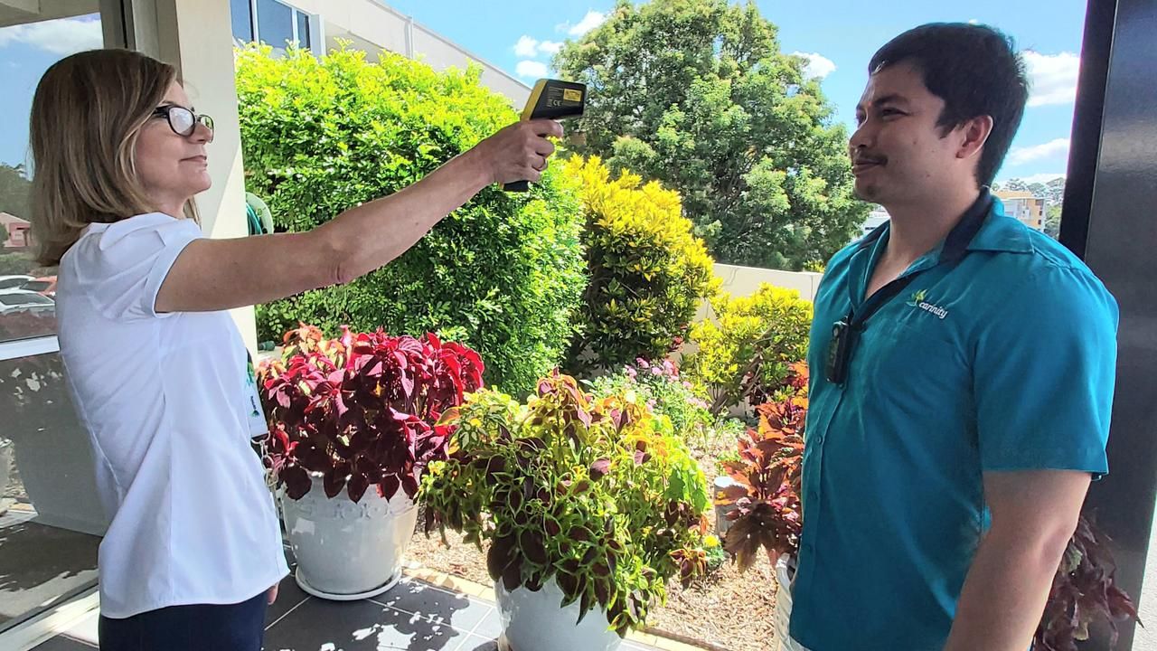 Carinity Hilltop aged care community staff member takes the temperature of work colleague Mark Rosales.