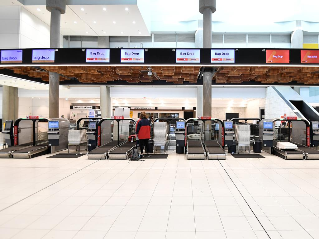 A lone passenger is seen using the self check-in at the Jetstar terminal at Brisbane Airport. Travel bans are keeping the COVID-19 spread down in Australia. Picture: AAP