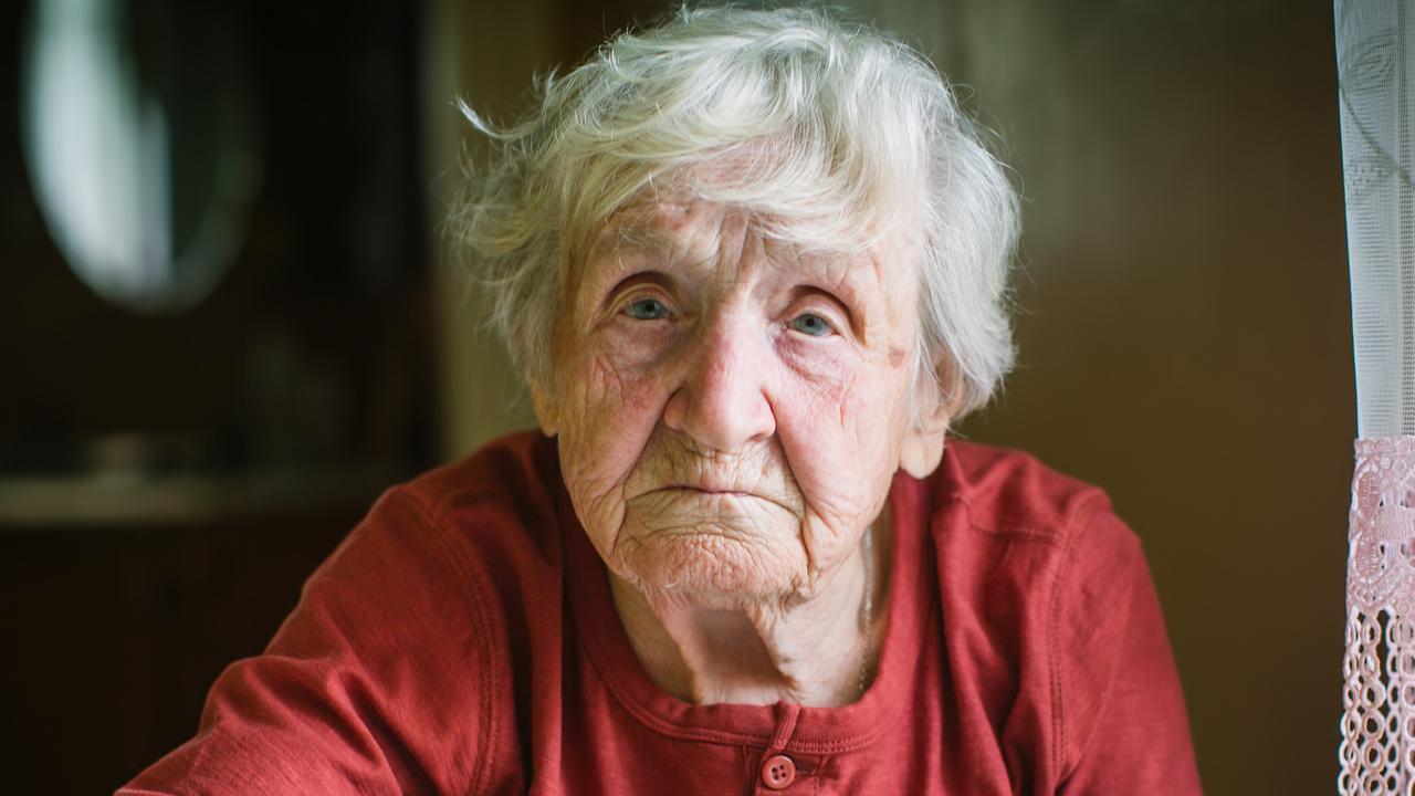 Elderly woman eats buckwheat porridge sitting at the table.