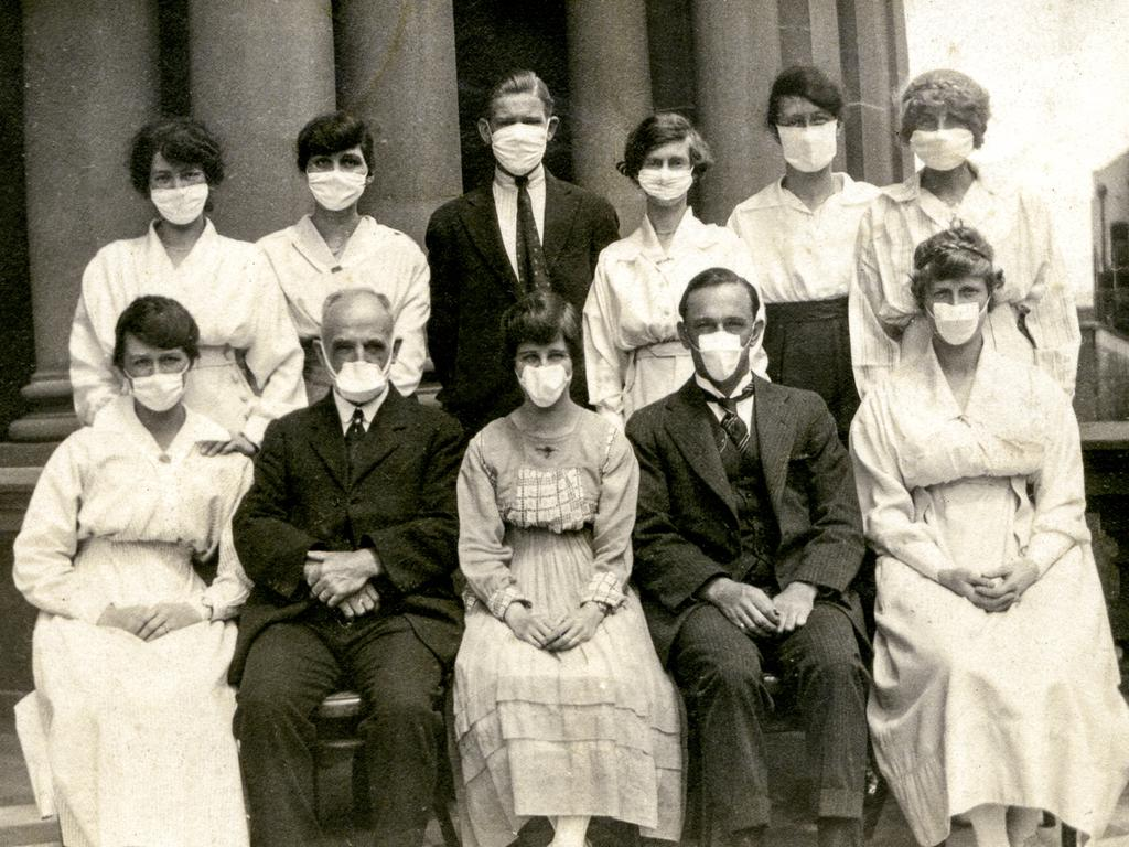 Masked figures at Sydney Town Hall during the height of the epidemic. Picture: City of Sydney Archives