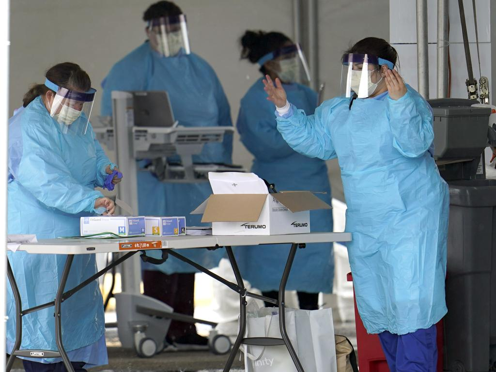 Medical professionals put on new gloves after washing their hands at a newly opened drive-thru testing site for COVID-19 Friday, March 20, 2020, in Houston, Texas. Picture: AP