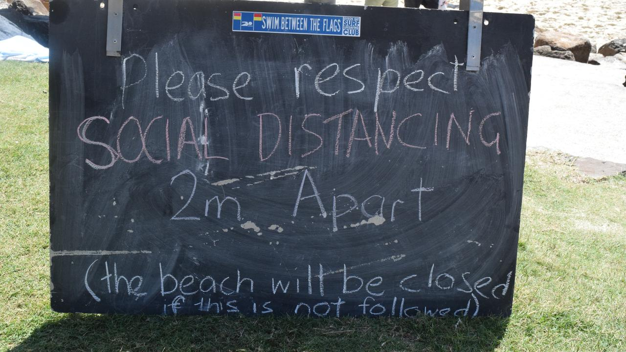 Sign at Byron's Main Beach warns people to keep their distance.