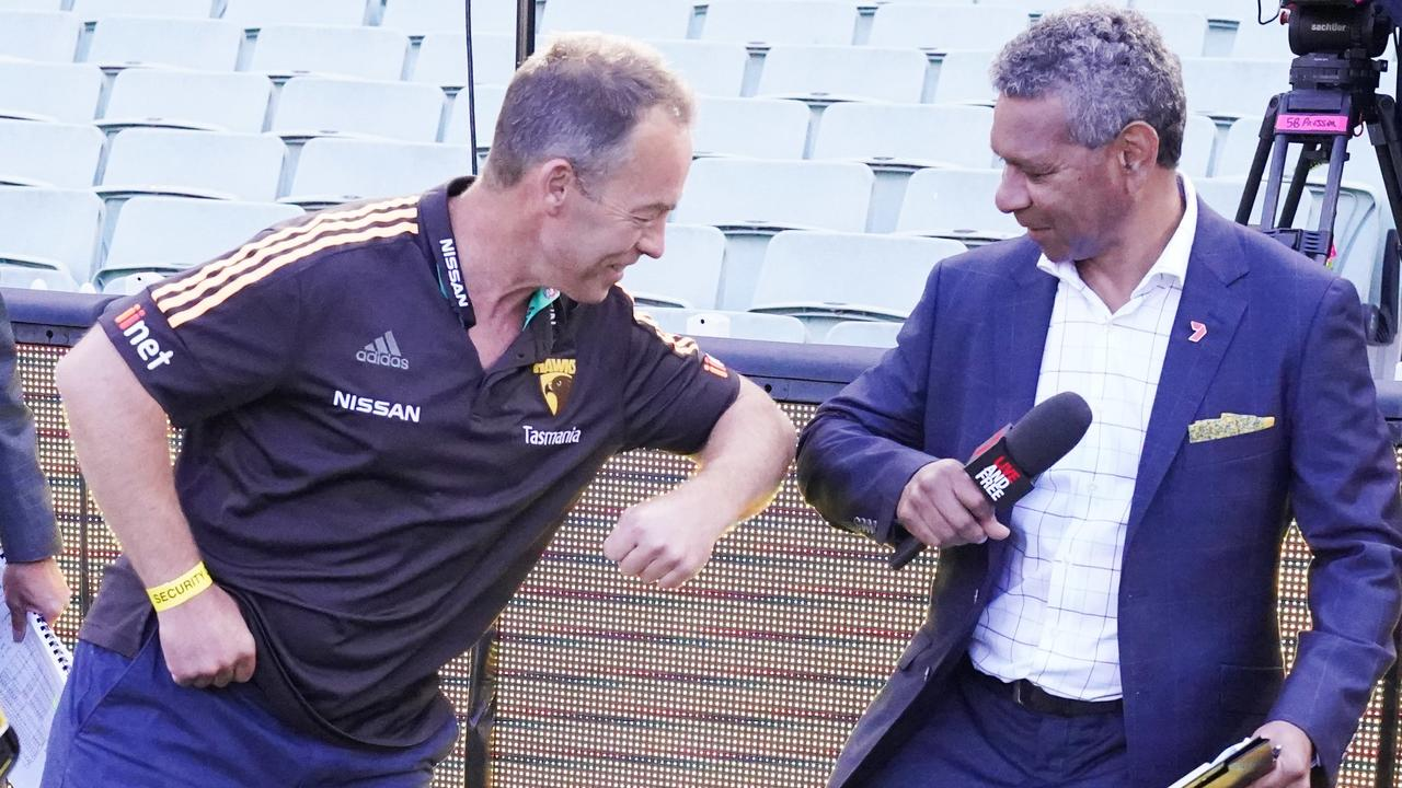 Clarko knocks elbows with former Brisbane Lion and TV commentator Gilbert McAdam. Picture: AAP