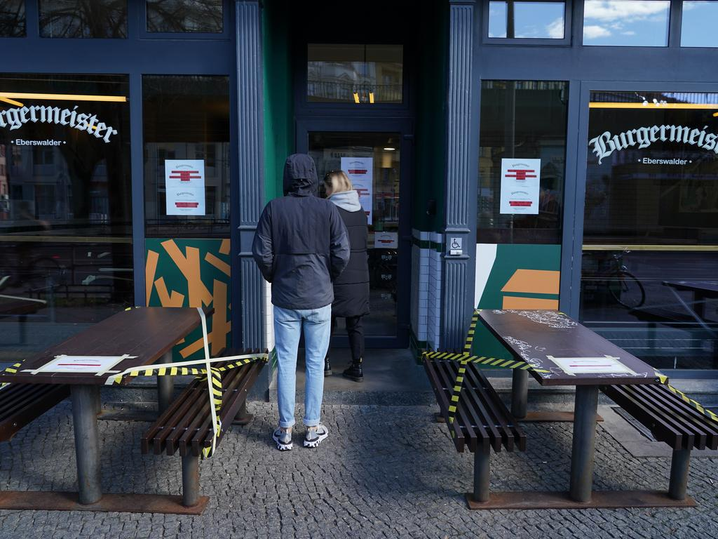 Customers wait to buy takeaway at a burger restaurant otherwise closed to slow the spread of the coronavirus in Berlin. The same will follow across Australia after strict lockdown measures take effect today. Picture: Getty Images