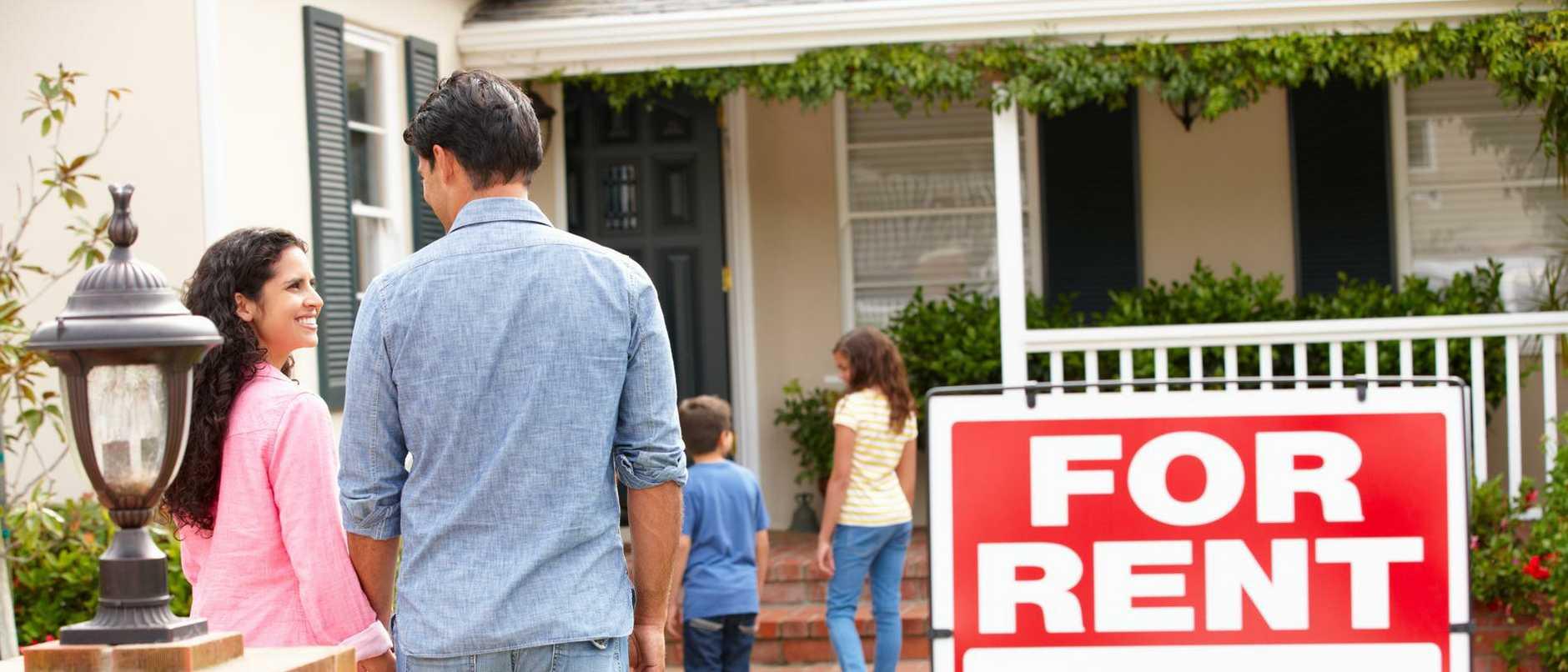 Smiling Hispanic family outside rental home