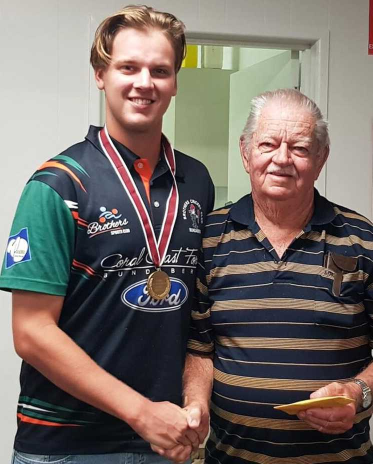 Brothers player Sam Pearson accepts the Don Tallon medal from Ray Haylock, who is a life member and patron of the Bundaberg Cricket Association.