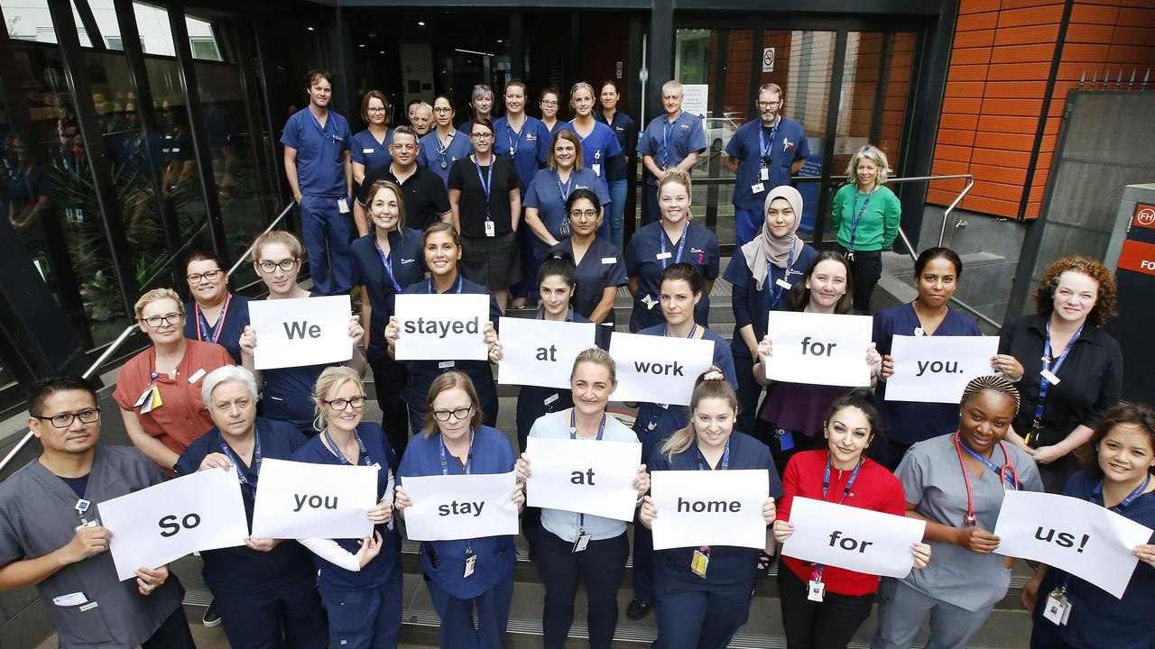 Royal Melbourne Hospital staff gather outside the main entrance urging people top stay at home. Picture: David Caird