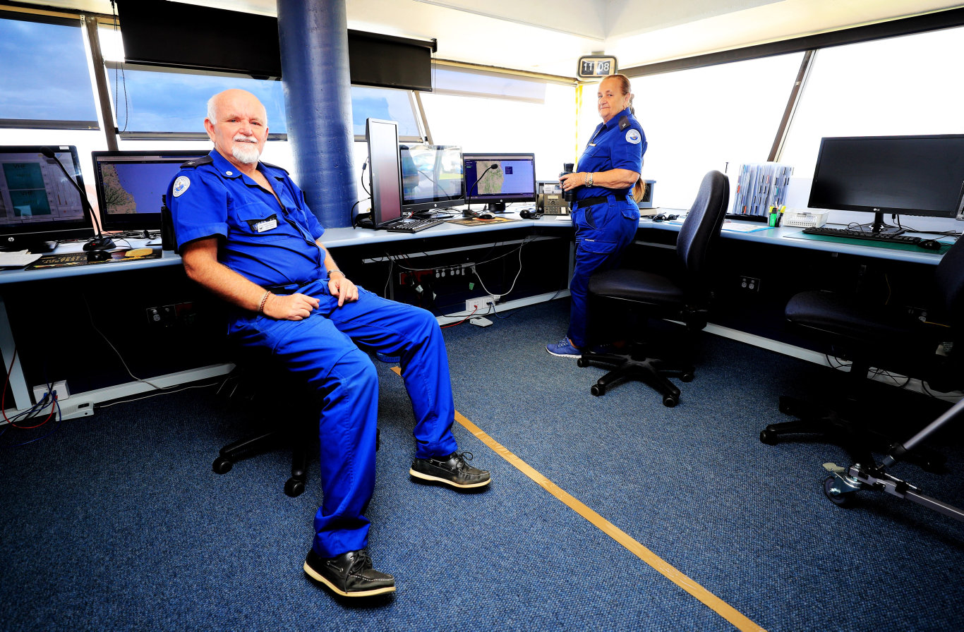 Point Danger Volunteer Marine Rescue OfficersGary Burcher and Beryl Aldred sit either side of the NSW / Queensland border which runs right through the middle of their Rescue Radio room at Point Danger. Photo: Scott Powick