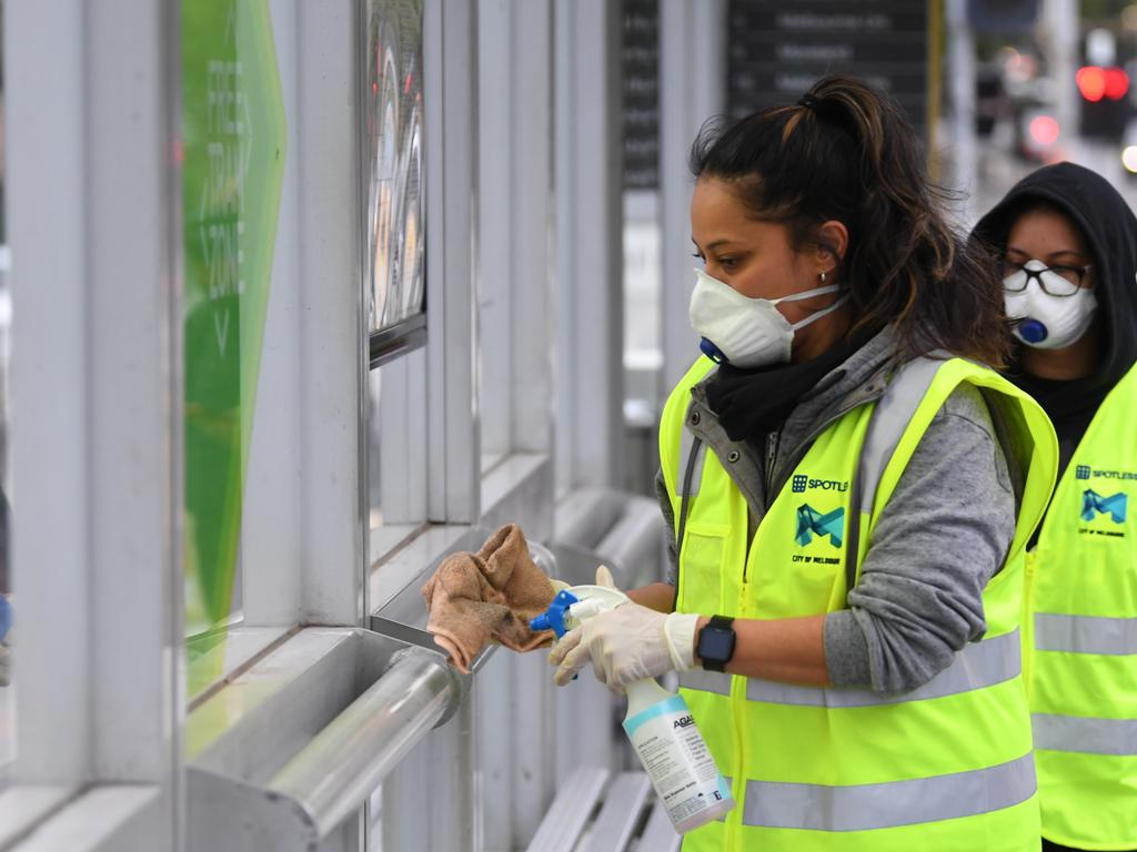 A member of a cleaning team is seen working at tram shelter in Melbourne this morning. Picture: James Ross/AAP