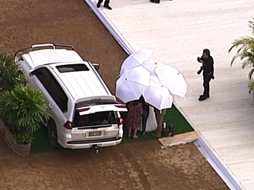 Bindi is shielded by umbrellas. Picture: 7News