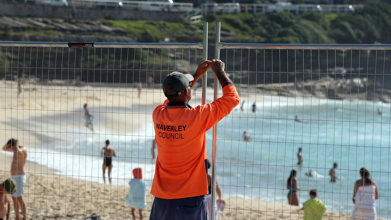 A Waverley Council worker fences off Bondi Beach, one of the areas worst affected by coronavirus in Australia.