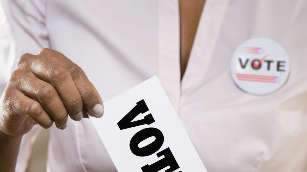 A woman voting at a ballot box.