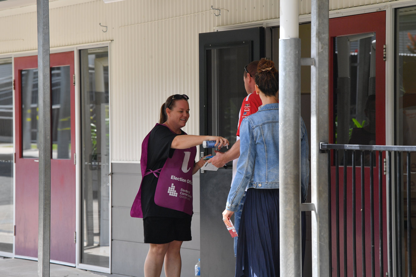 Polling at Woombye State School. ECQ volunteer Deanne Dow administers hand sanitiser. Photo: John McCutcheon / Sunshine Coast Daily