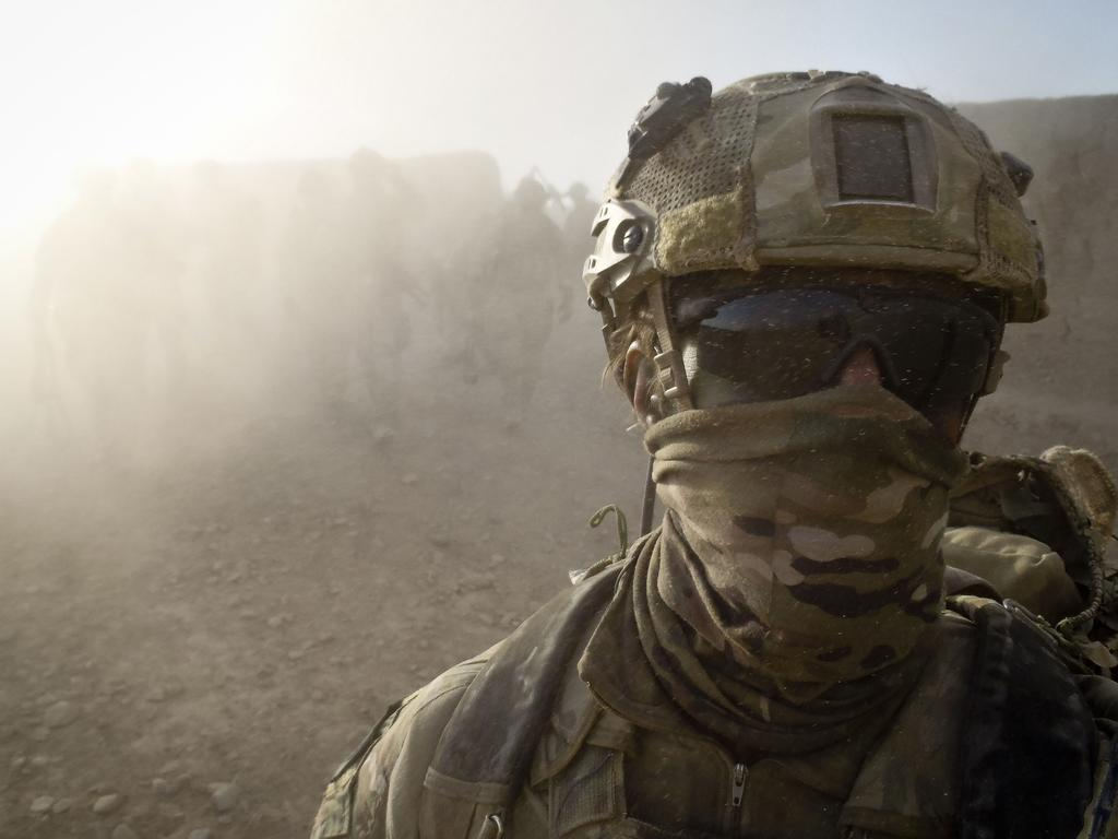 An Australian Special Forces soldier walks ahead of his Afghan National Security Force and Australian Special Operations Task Group comrades.