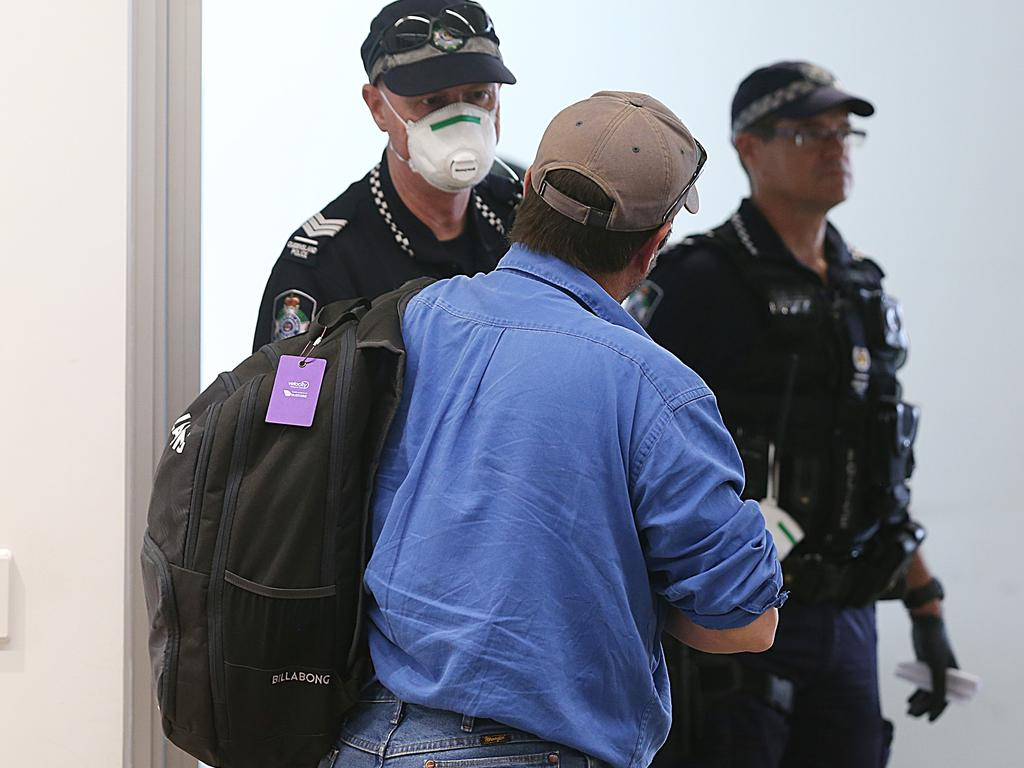Federal and Queensland police greeting passengers of a Qantas flight coming in from Sydney to check they know the quarantine rules. Picture: Stewart McLean