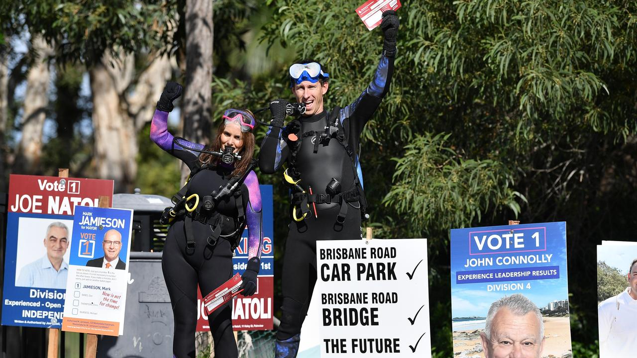 SUITED UP: Shara Smith and Mike McKinnon out in safety mode in full scuba diving gear for their vote at Mooloolaba State School. Photo Patrick Woods / Sunshine Coast Daily.