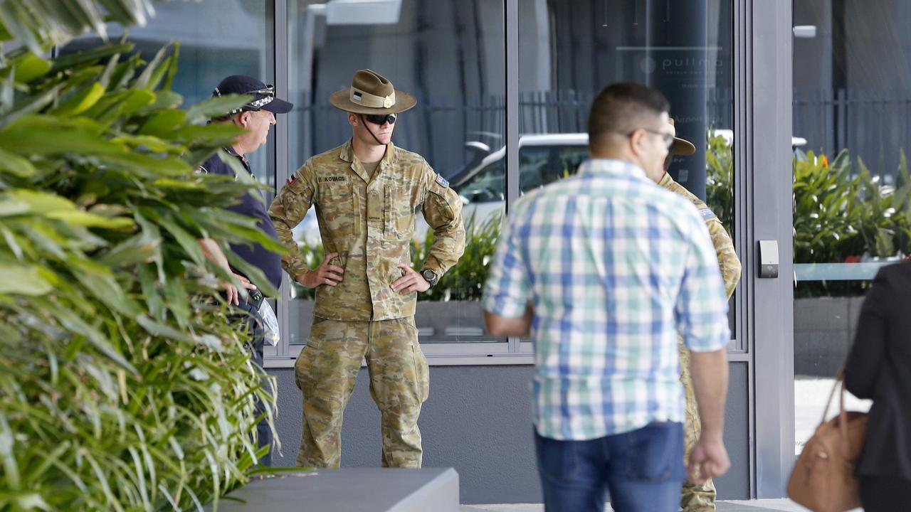 Police and Army personnel watch as Passengers arriving into Brisbane International Airport and forced into quarantine. Passengers getting off and being taken to buses before taken to hotels to quarantine, Sunday 29th March 2020 – Photo Steve Pohlner