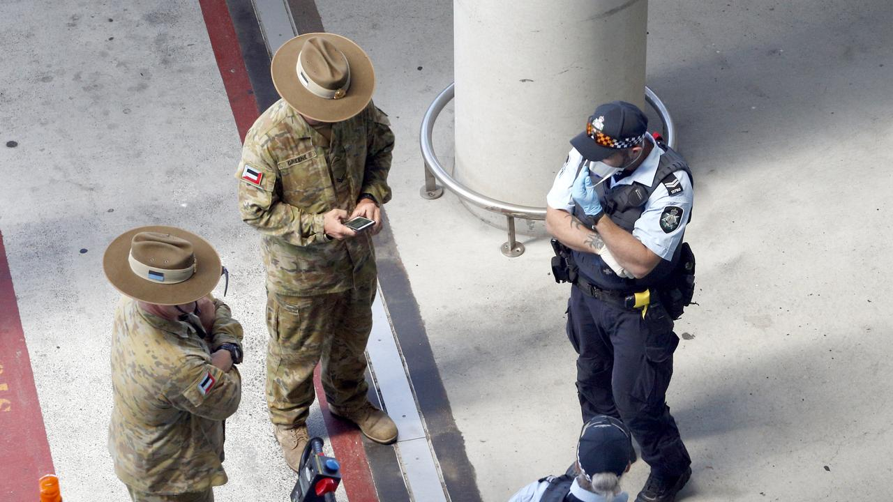 Police and Army personnel watch as passengers arrive into Brisbane International Airport Picture: Steve Pohlner