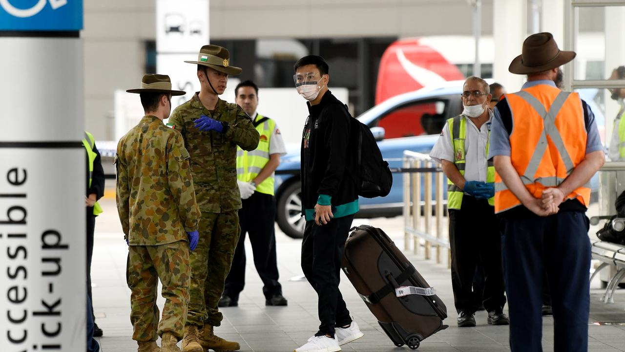 Australian Defence Force personnel watch over returning overseas travellers at Sydney International Airport in Sydney on Monday, March 30, 2020. Picture: Bianca De Marchi/AAP