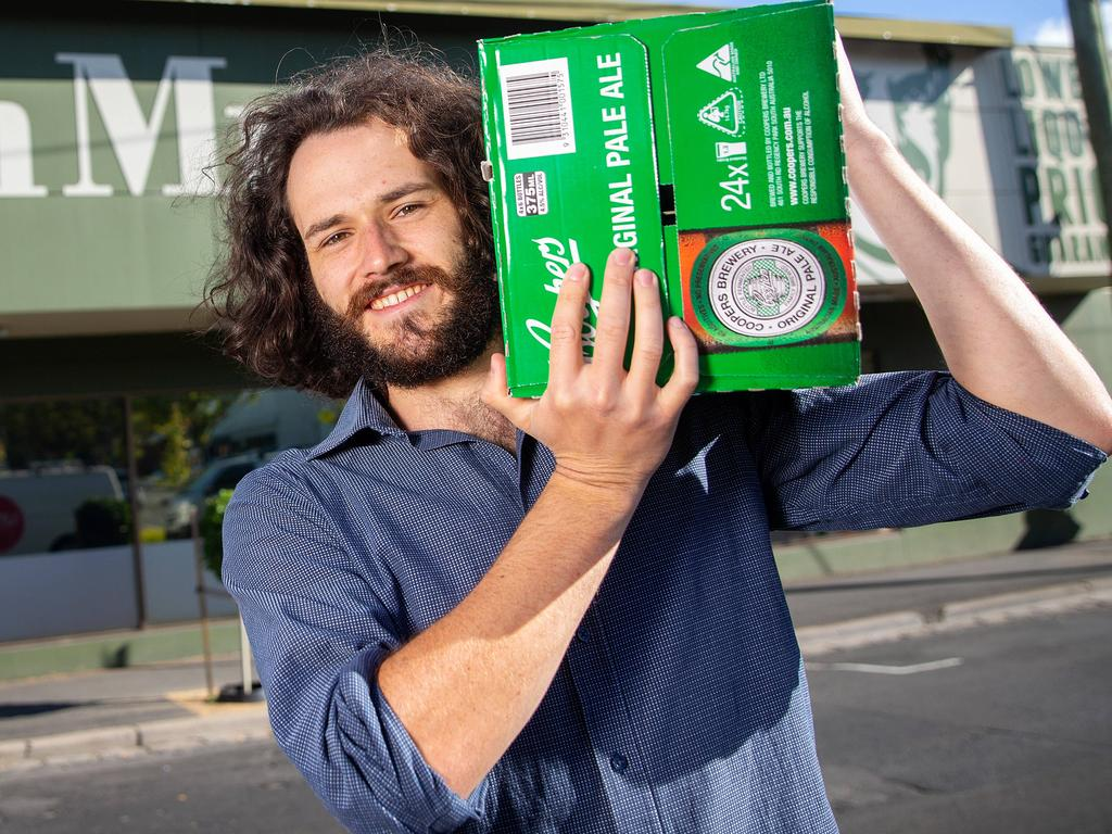 Harry Vincent and his case of beer after Dan Murphy's announces it will be further restricting customers to counteract stockpiling among customers. Picture: Mark Stewart