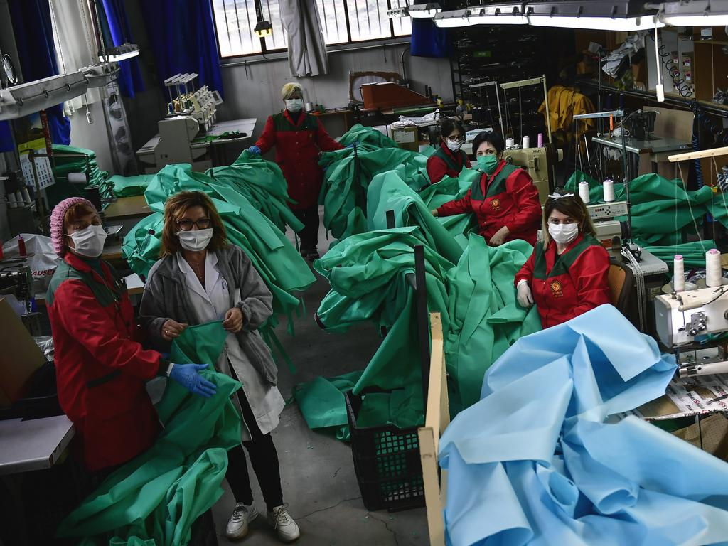 Volunteer workers in a clothing factory manufacturing firefighting gear, pose for a photo as they make hospital gowns for medical staff to protect them from the coronavirus, in Arnedo, northern Spain. Picture: AP