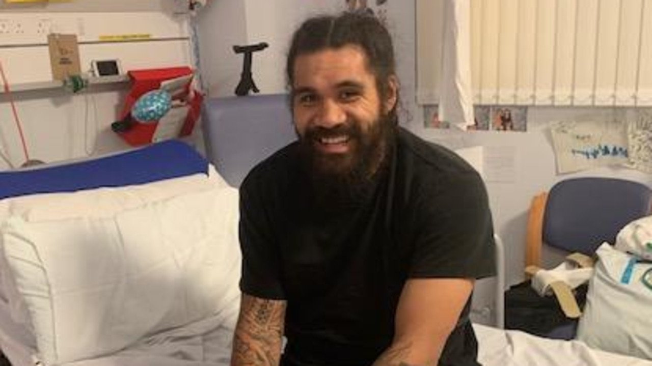 Mose Masoe sits up in his hospital bed