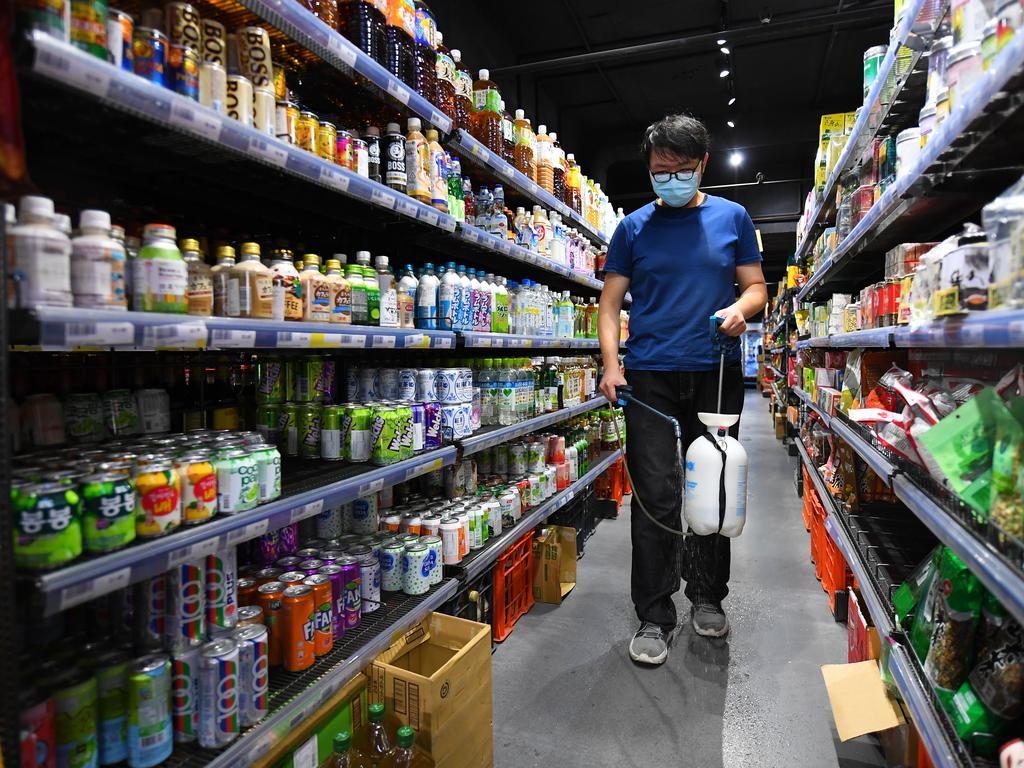 An employee of Great Asia food store sprays disinfectant as a preventive measure against coronavirus in Melbourne. Picture: AAP